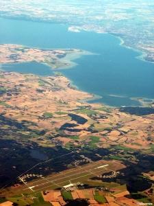 """Aarhus lufthavn med Aaarhusbugten og selve byen i bakgrunnen. Flyplassen ligger ved Tirstrup i Jylland - 45 kilometer fra selve byen og 16 kilometer fra """"molbohovedstaden"""" Ebelstoft. (foto: Aarhus lufthavn sett ovenfra (foto: ©otoerres))"""
