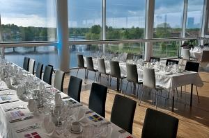 Uppdukade långbord på Karlstad CCCs 5e våning med en fantastisk vy över Klarälven. (KCCC)